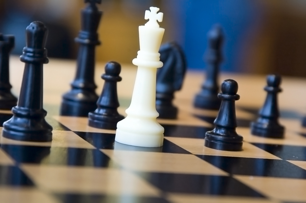 White king and black opponents on chessboard